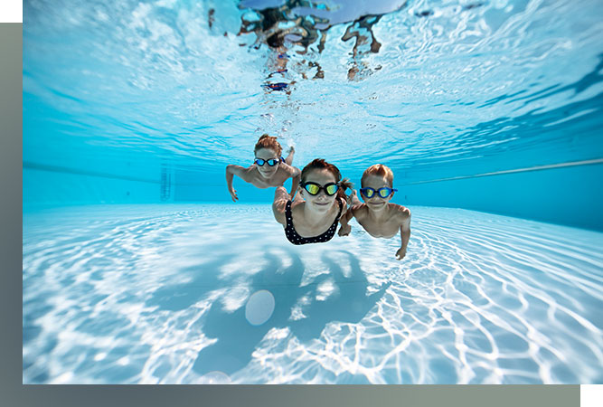 underwater image of the smiling kids, swimming in a pool