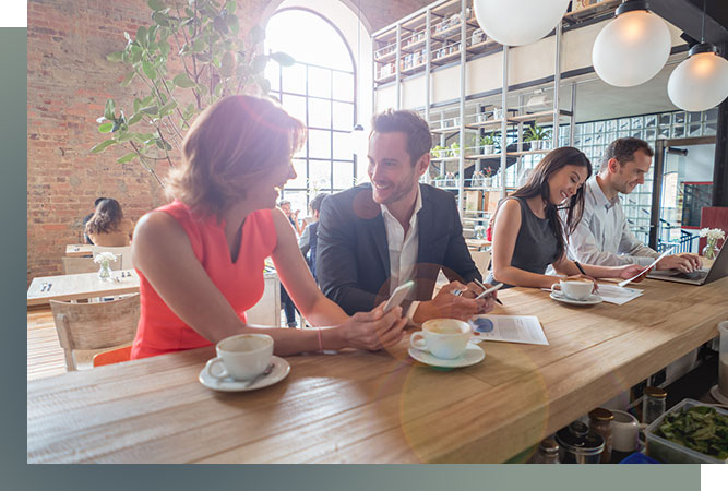 four young professionals at a restaurant. Working and having coffee